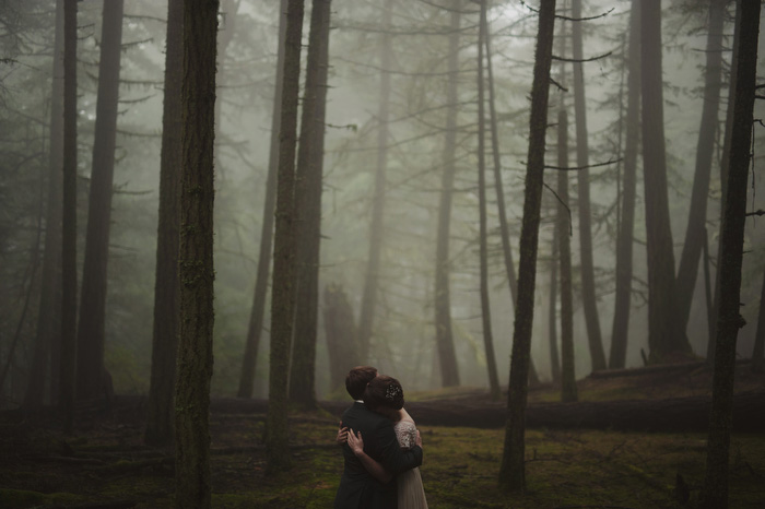 bride and groom hugging in foggy woods