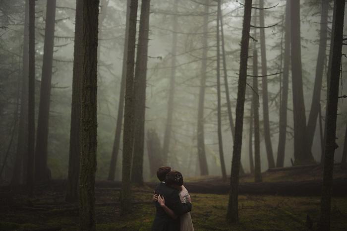 bride and groom hugging in foggy woods