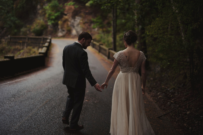 bride and groom walking down forest path