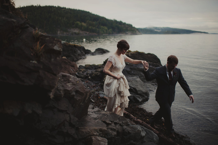 bride and groom walking on the rocks