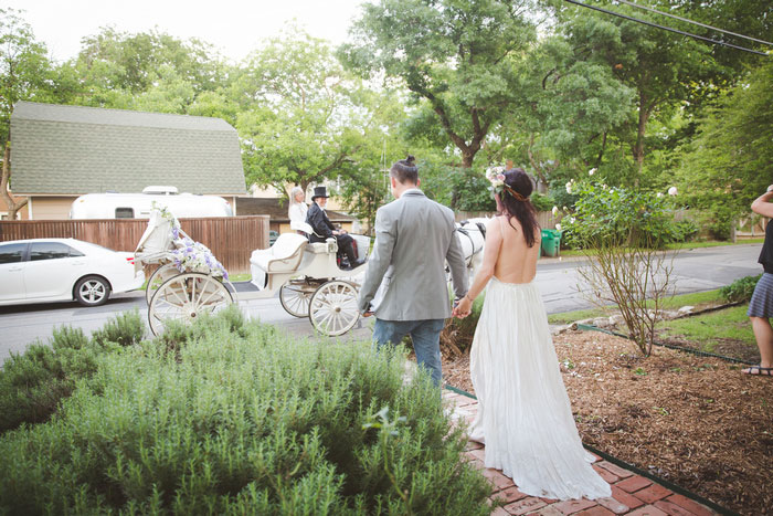 brie and groom walking toward horse drawn carriage