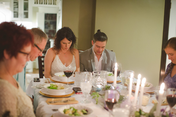 bride and groom bowing heads at dinner