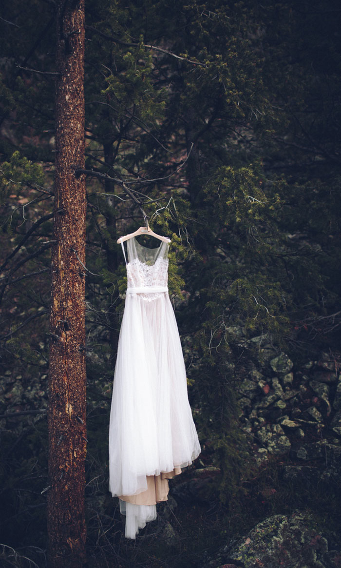 wedding dress hanging in the woods