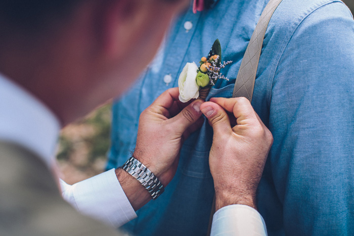 boutonniere being pinned on groom
