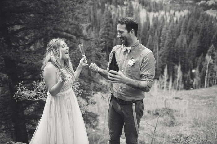 bride and groom celebrating on mountainside