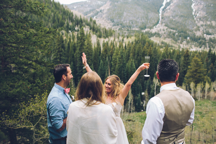 bride and groom celebrating on mountainside