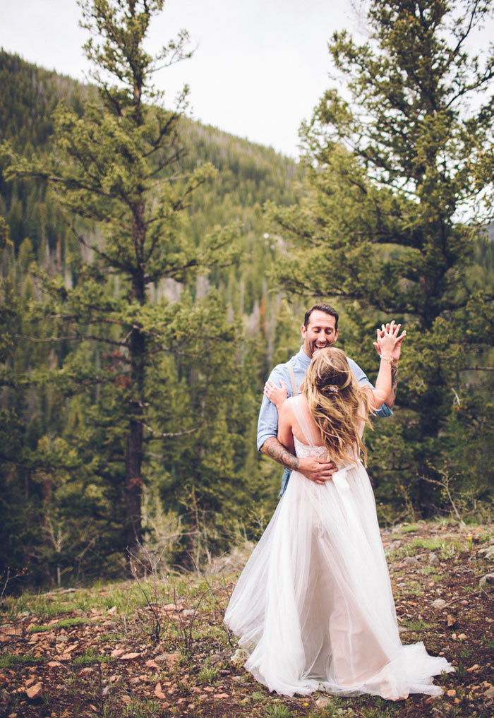 bride and groom dancing on mountainside