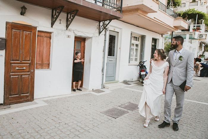 bride and groom walking down greek village street