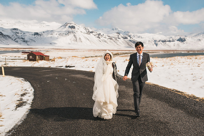 bride and groom walking down iceland road