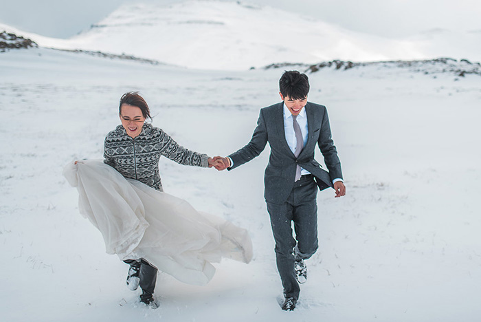 bride and groom walking through snow in Iceland