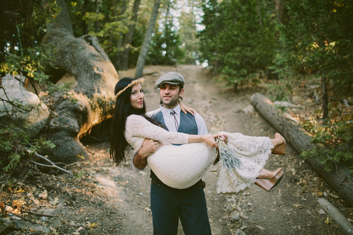 groom carrying bride down mountain