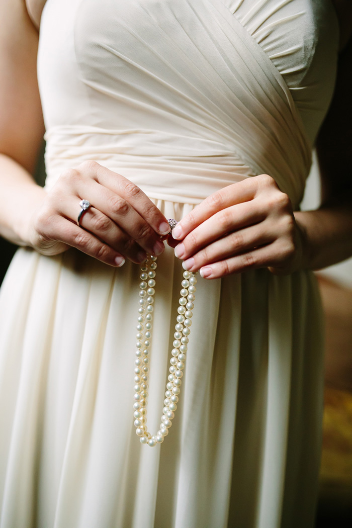 bride holding pearl necklace