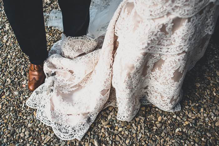 detail of bottom of bride's dress and groom's shoes