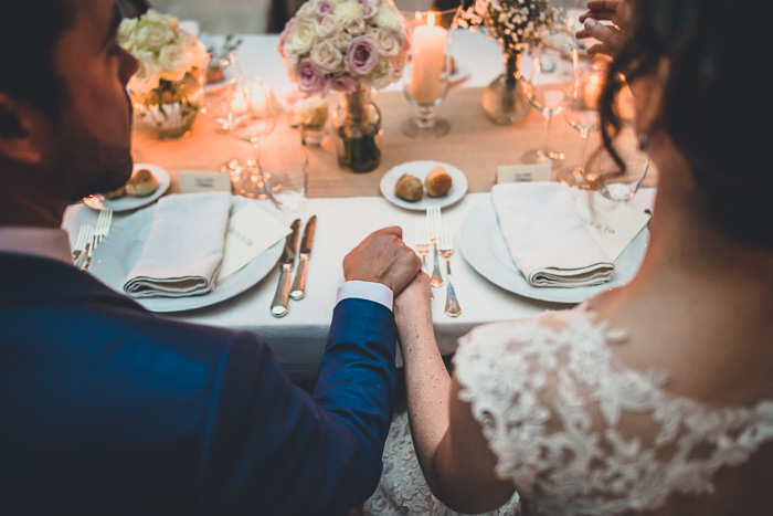 bride and groom holding hands during reception dinner
