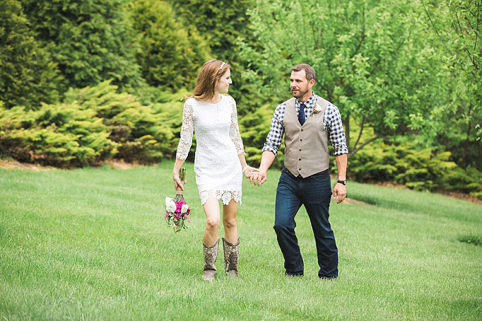 bride and groom waking across grass