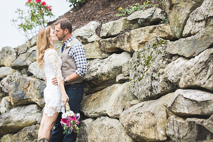 bride and groom kissing by rocks