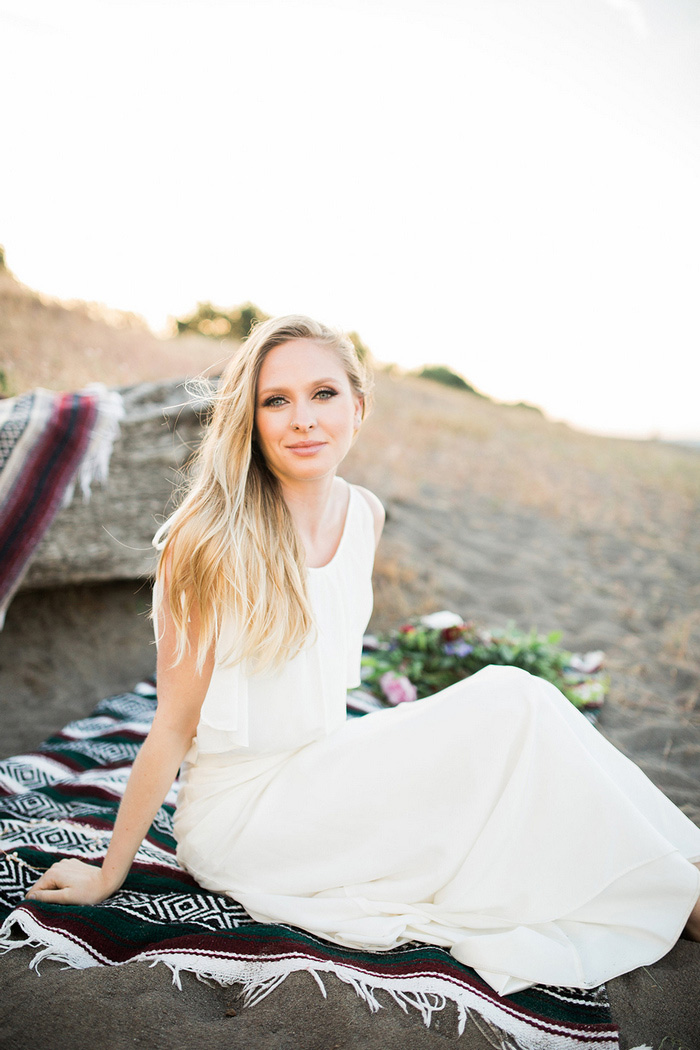 bride sitting on beach blanket