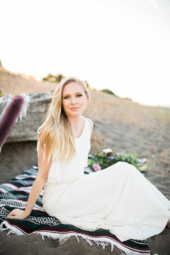 bride sitting on beach blanket