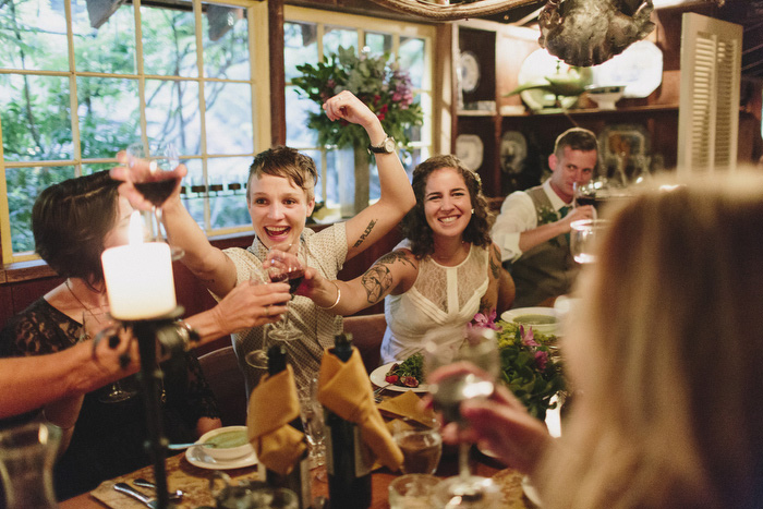 brides toasting with guests at reception dinner