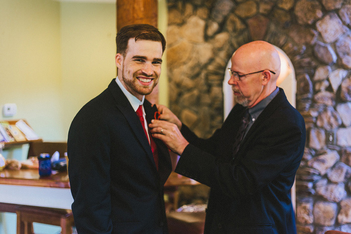 groom having his boutonniere pinned on