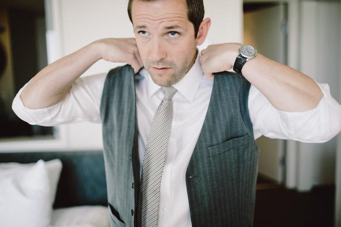 groom putting on vest