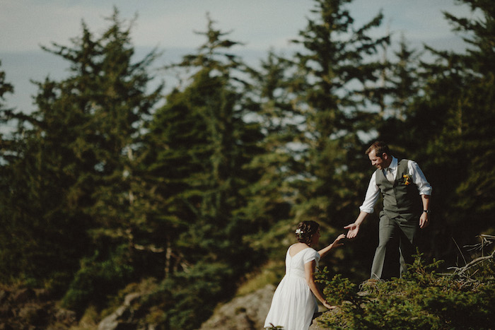 groom helping bride climb the rocks