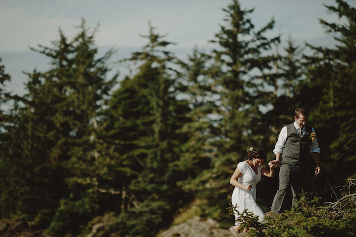 bride and groom climbing on rocks