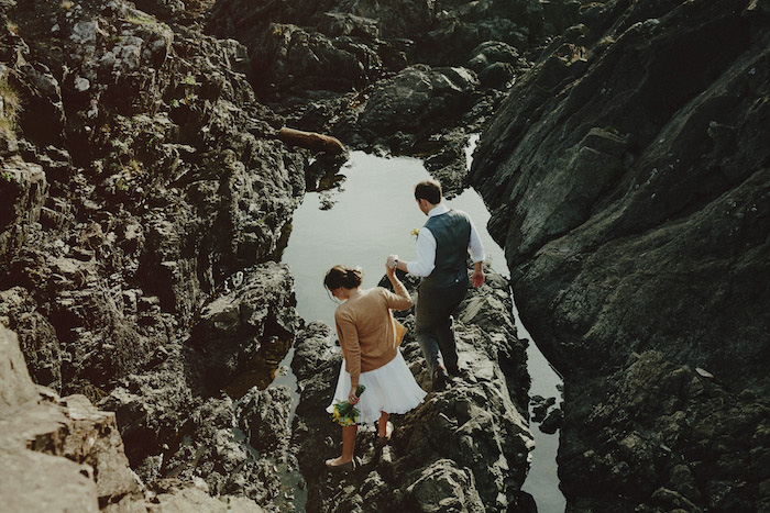 bride and groom walking on the rocks