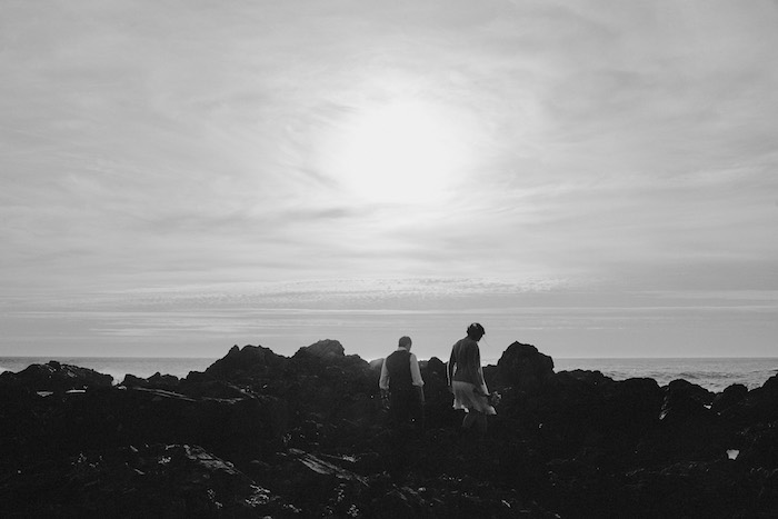 bride and groom climbing on rocks