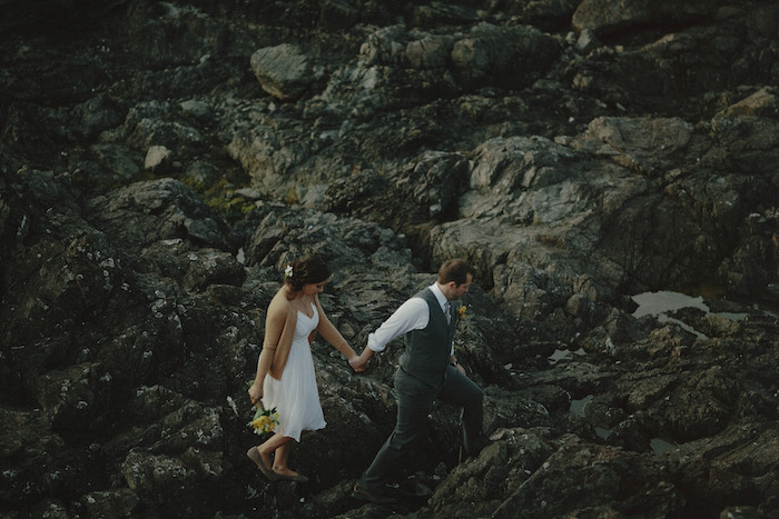 bride and groom walking on rocky coast