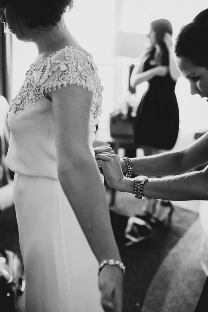 bride getting buttoned into her dress