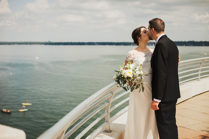bride and groom kissing by the waterfront