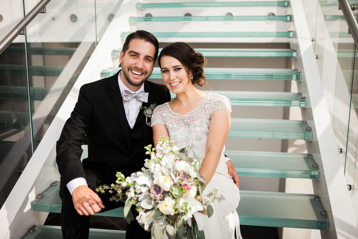 bride and groom sitting on glass steps