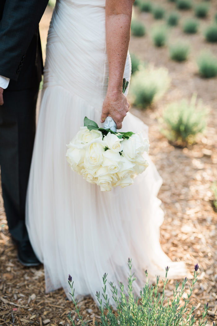 bride holding white wedding bouquet by her side