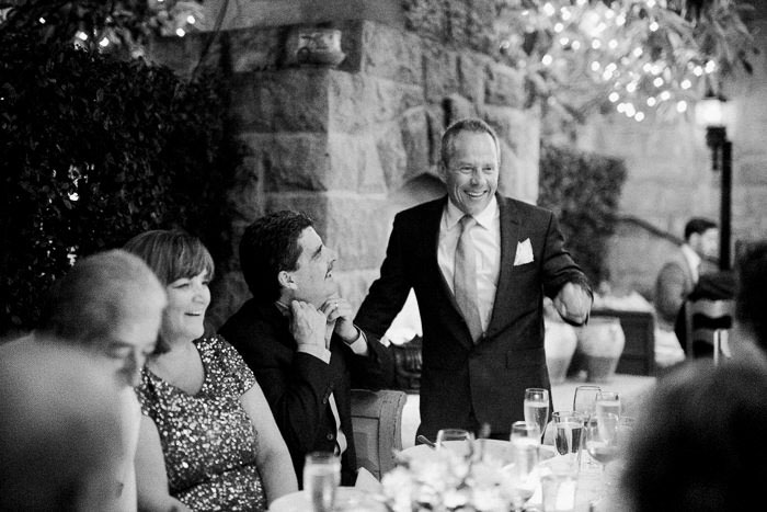 groom talking to guests at dinner