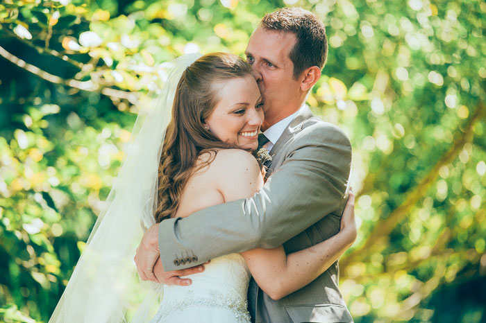 groom hugging and kissing bride on forehead