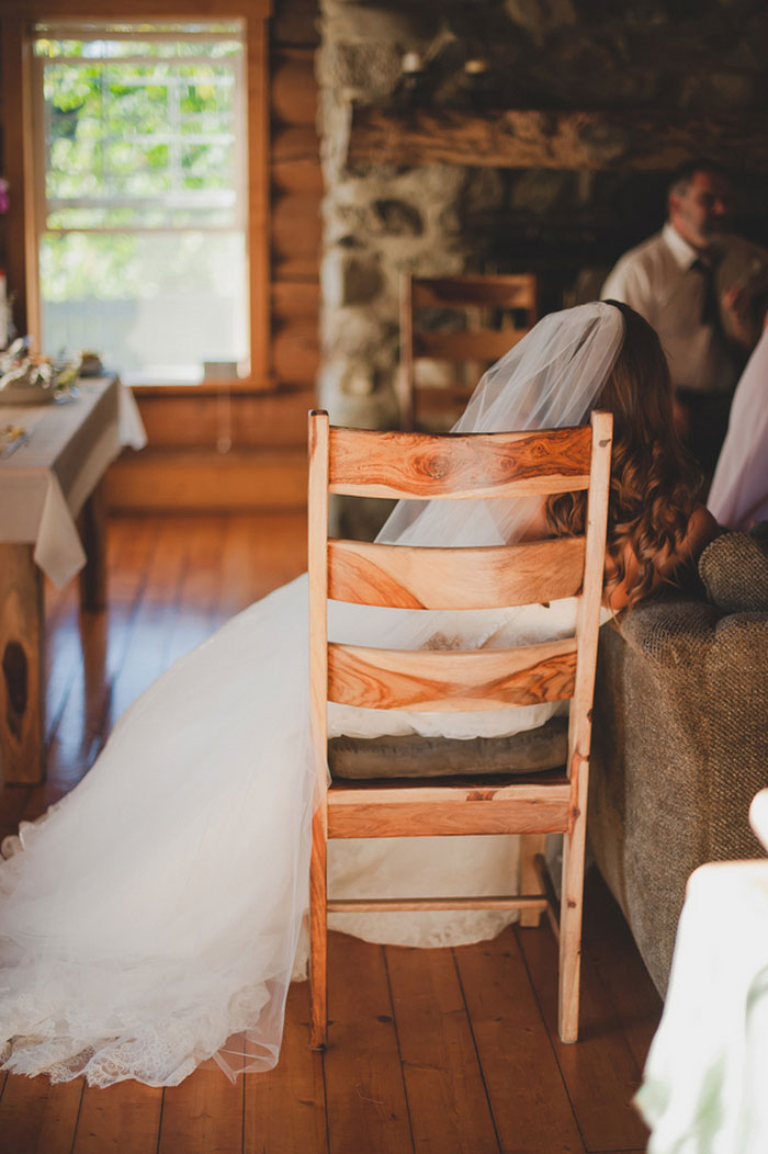 bride sitting on wooden chair in cabin