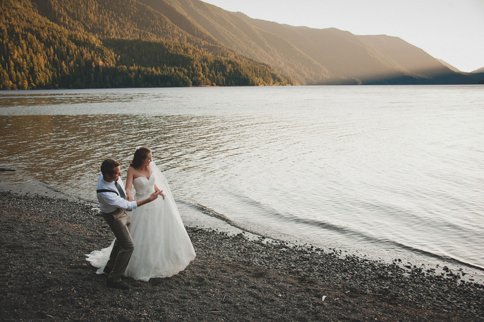 bride and groom skipping rocks on the lake