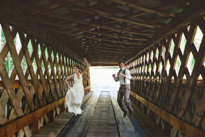 bride and groom jumping on covered bridge