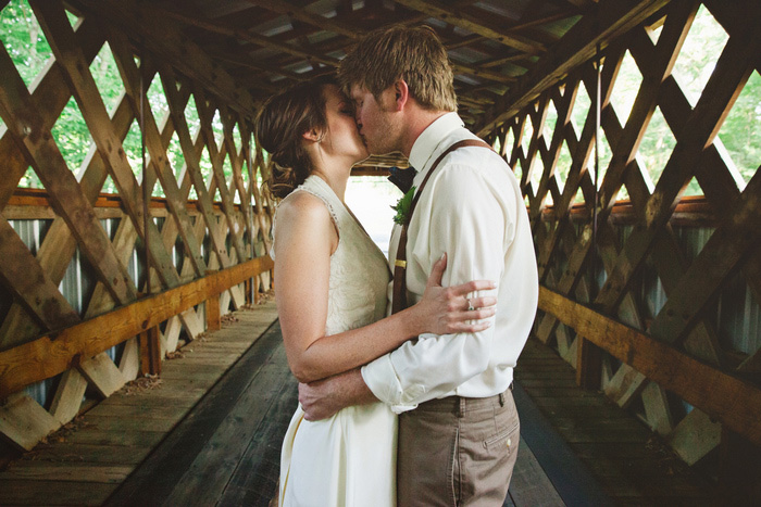 bride and groom kissing on covered bridge