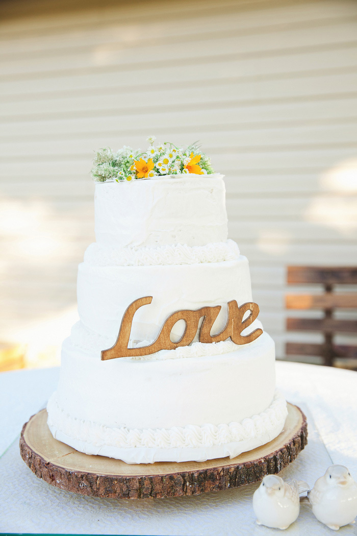 wedding cake with wild flowers and love sign