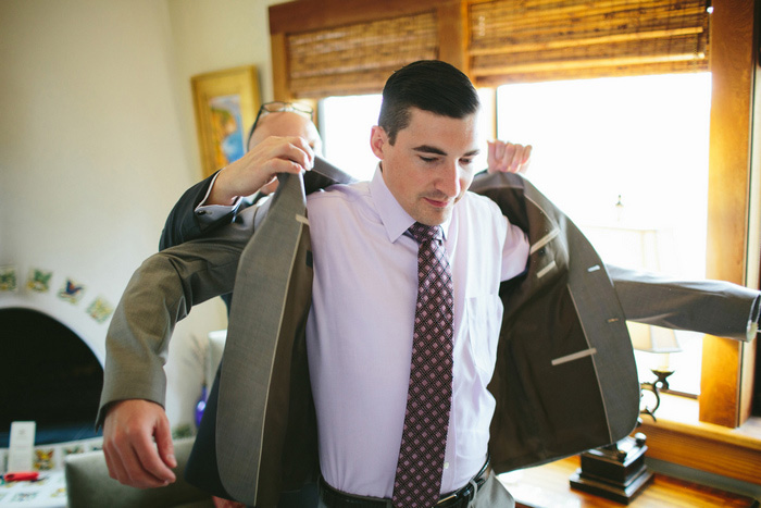 groom putting his jacket on