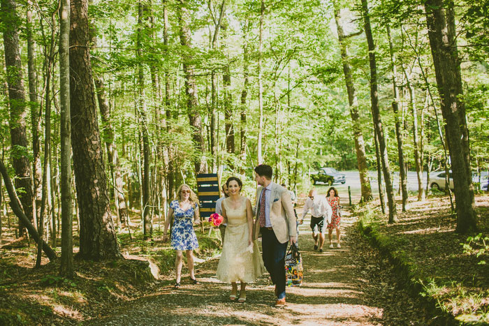 bride and groom walking to ceremony site in the woods