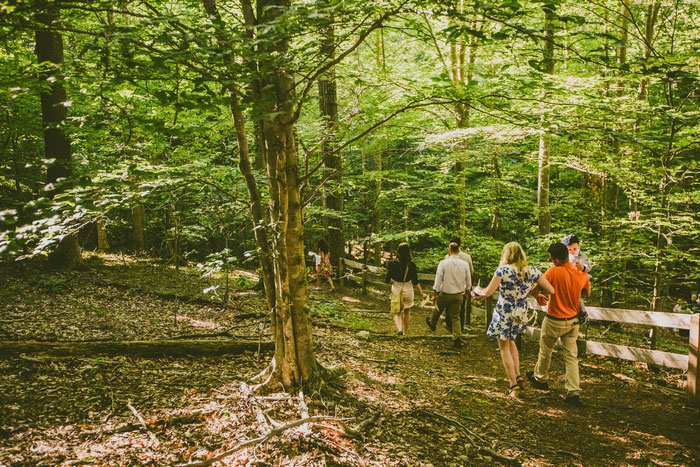wedding guests walking to ceremony site in the woods