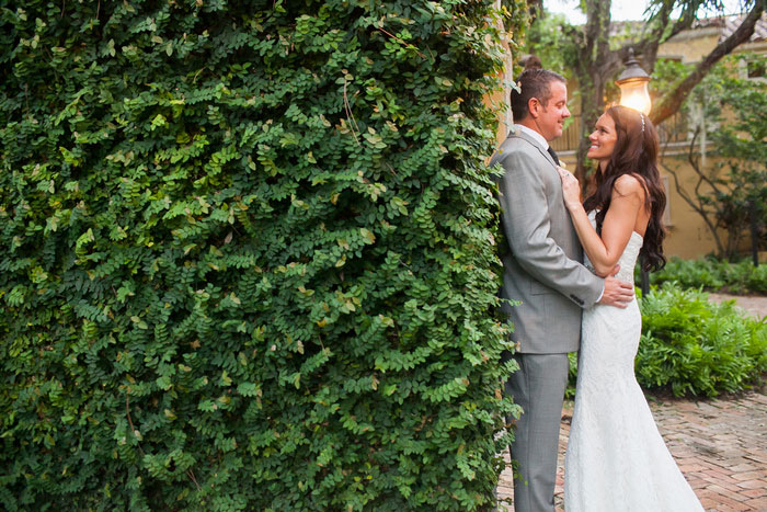 bride and groom portrait against ivy wall