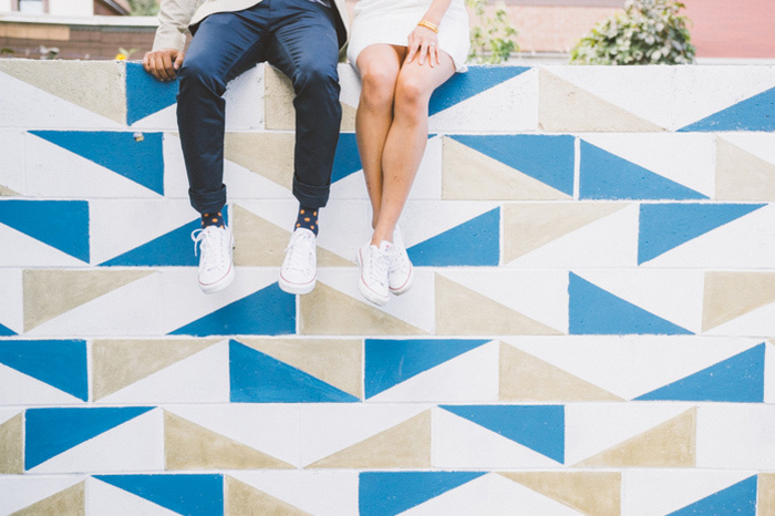 bride and groom sitting on colourful wall