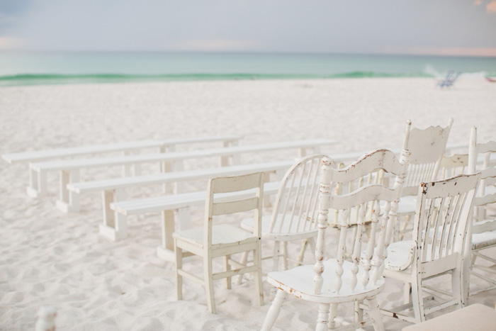white chairs set up on beach for ceremony