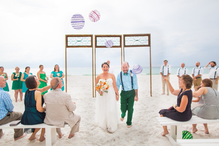 guests throwing beach balls at bride and groom at end of ceremony