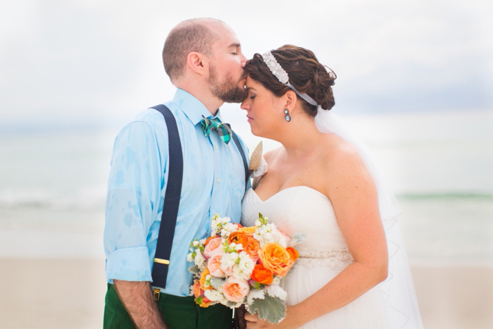 groom kissing bride on then forehead