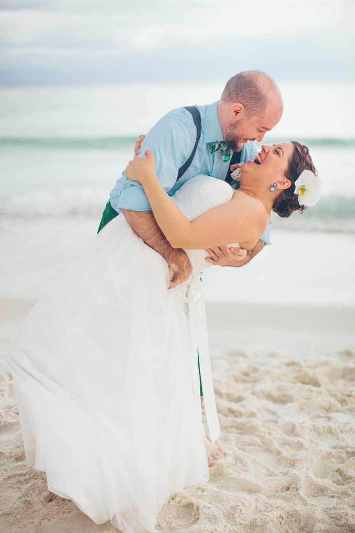 groom dipping bride on the beach